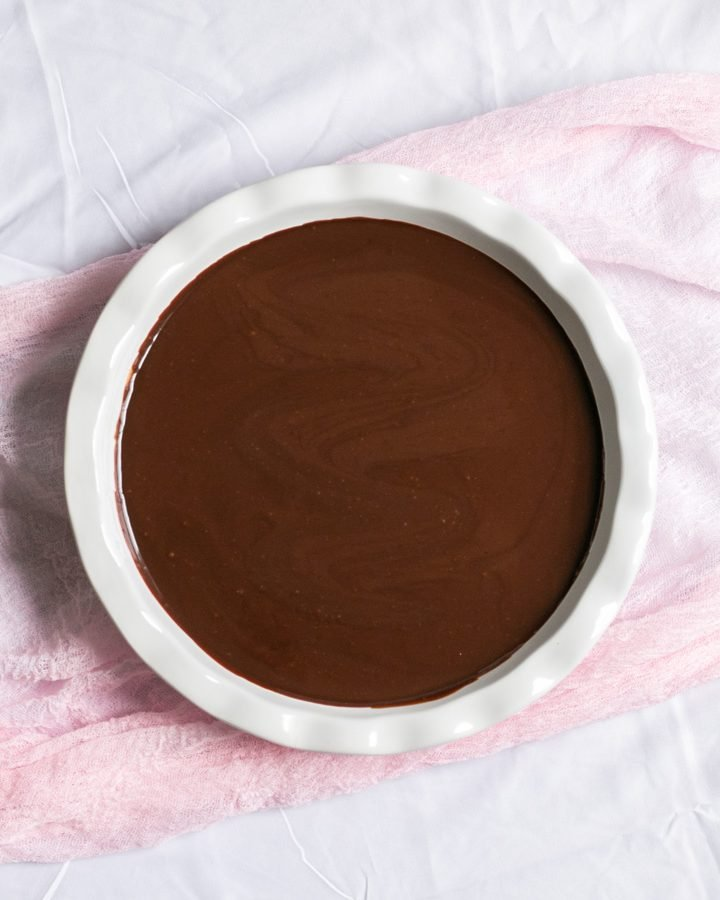 a white pie dish with chocolate ganache in it sitting on top of a pink cheese cloth