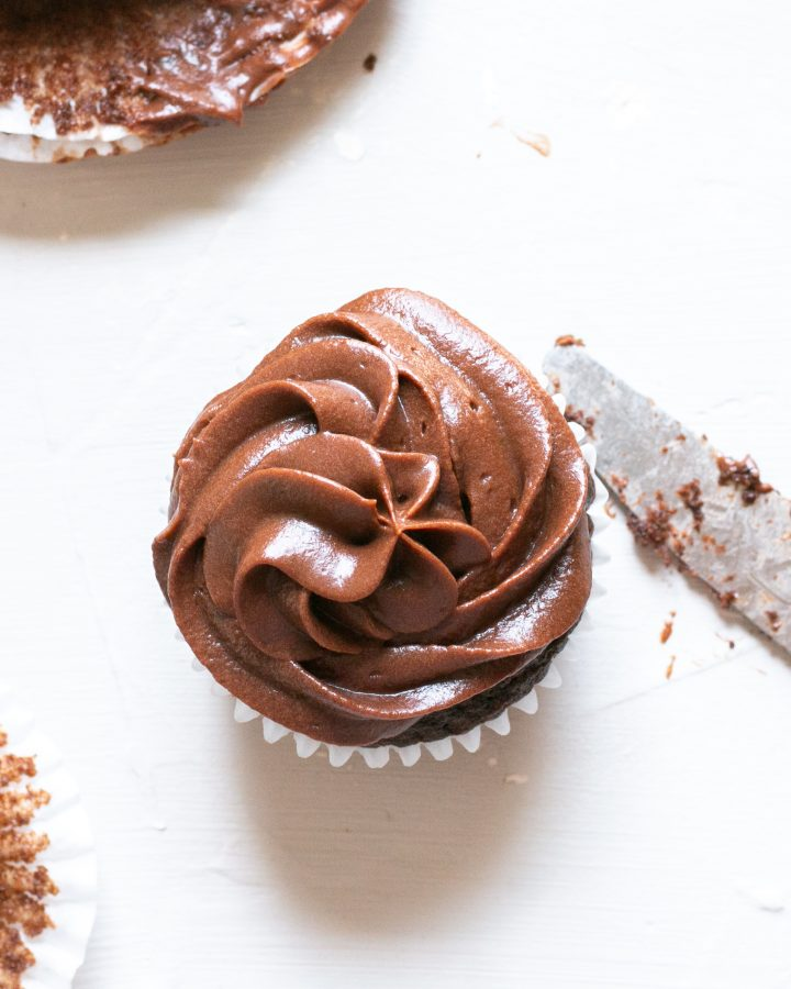 Chooclate buttercream piped onto a chocolate cupcake. A dirty knife is next to the cake