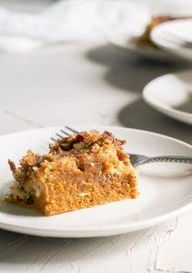 A piece of the pumpkin pie crunch dessert is on a white plate.