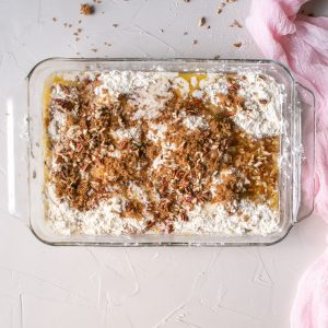 The yellow cake topping, chopped pecans, and brown sugar are sprinkled on top of the pumpkin pie crunch cake