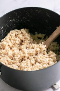 marshmallows and rice crispy cereal mixing in a large pot