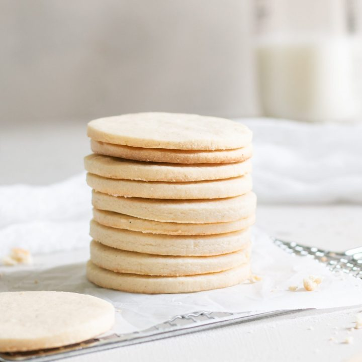 Stack of vanilla sugar cookie cutouts with one cookie in the foreground