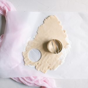 cutting out round sugar cookie cutouts