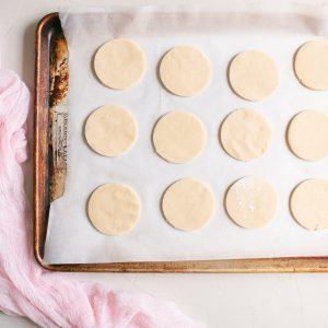 Placing the sugar cookie cutouts on a parchment paper lined baking sheet