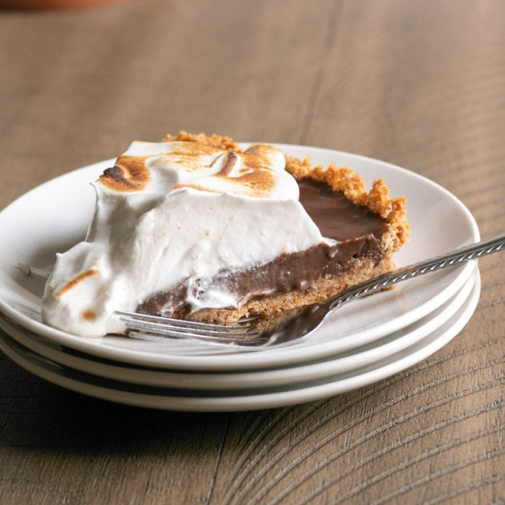 s'mores pie sitting on 3 stacked white plates.