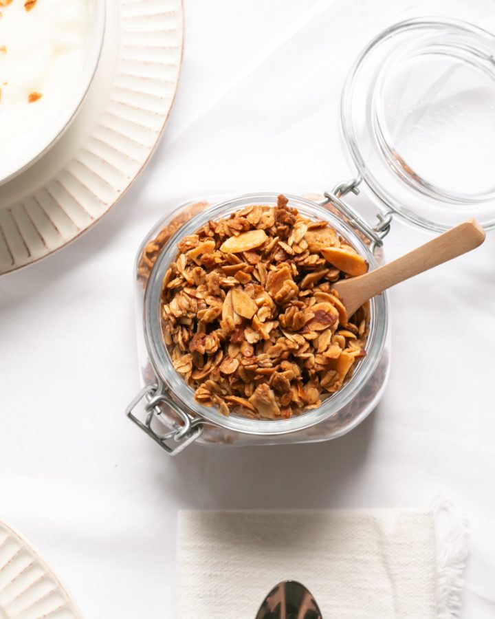 Vanilla Almond Granola inside a glass jar with a brown spoon