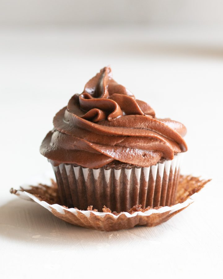 1 chocolate cupcake with buttercream frosting sitting on an open cupcake wrapper