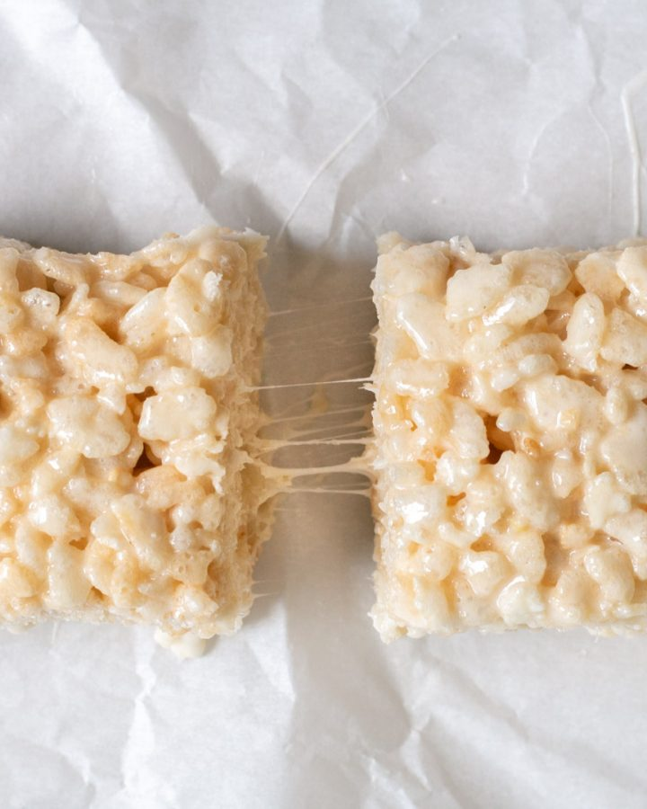 Two rice krispy treats sitting on parchment paper pulled apart to see the melted marshmallow